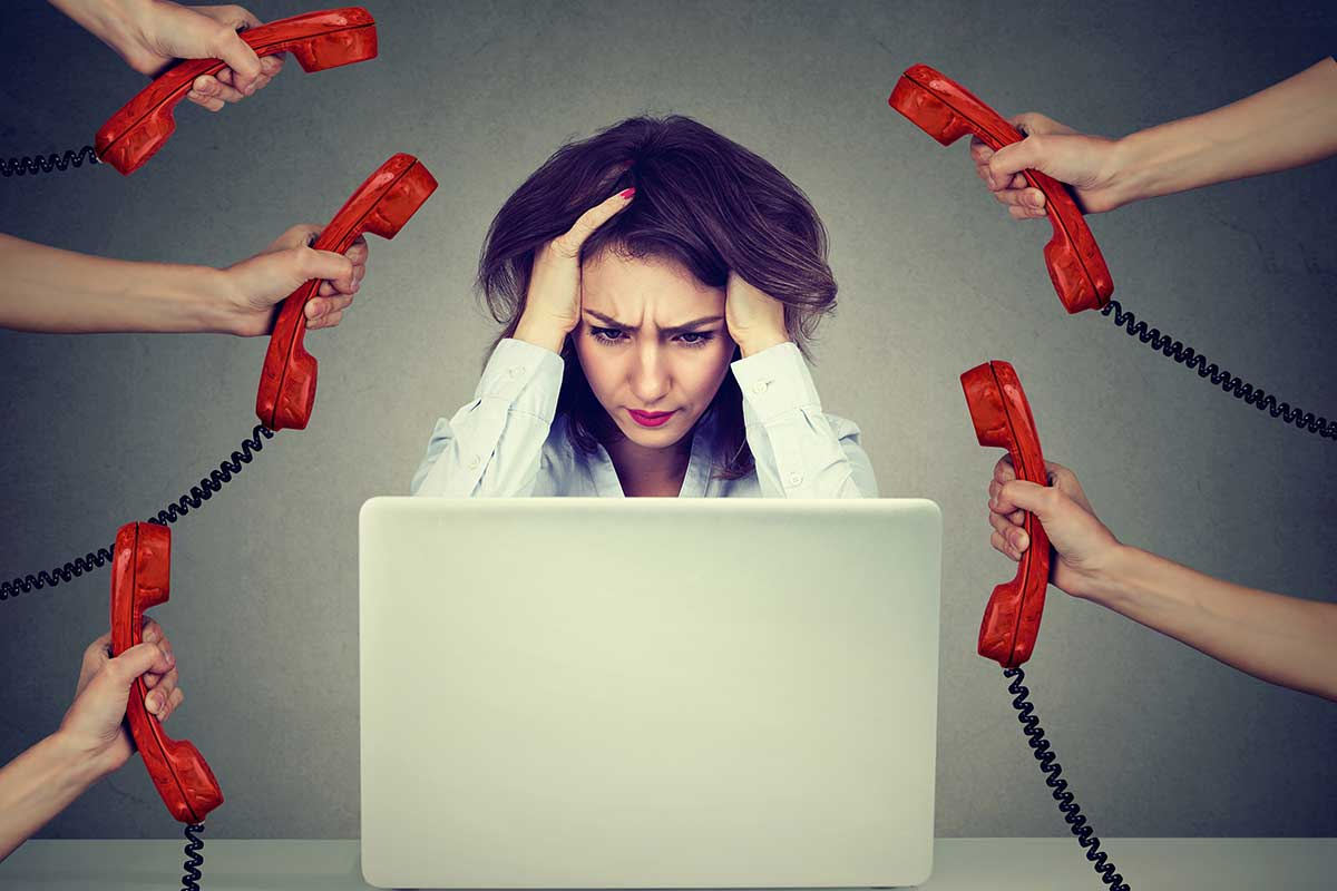 stressed out business woman with hands on head, looking at a laptop screen, and 5 hands holding phone handsets to her