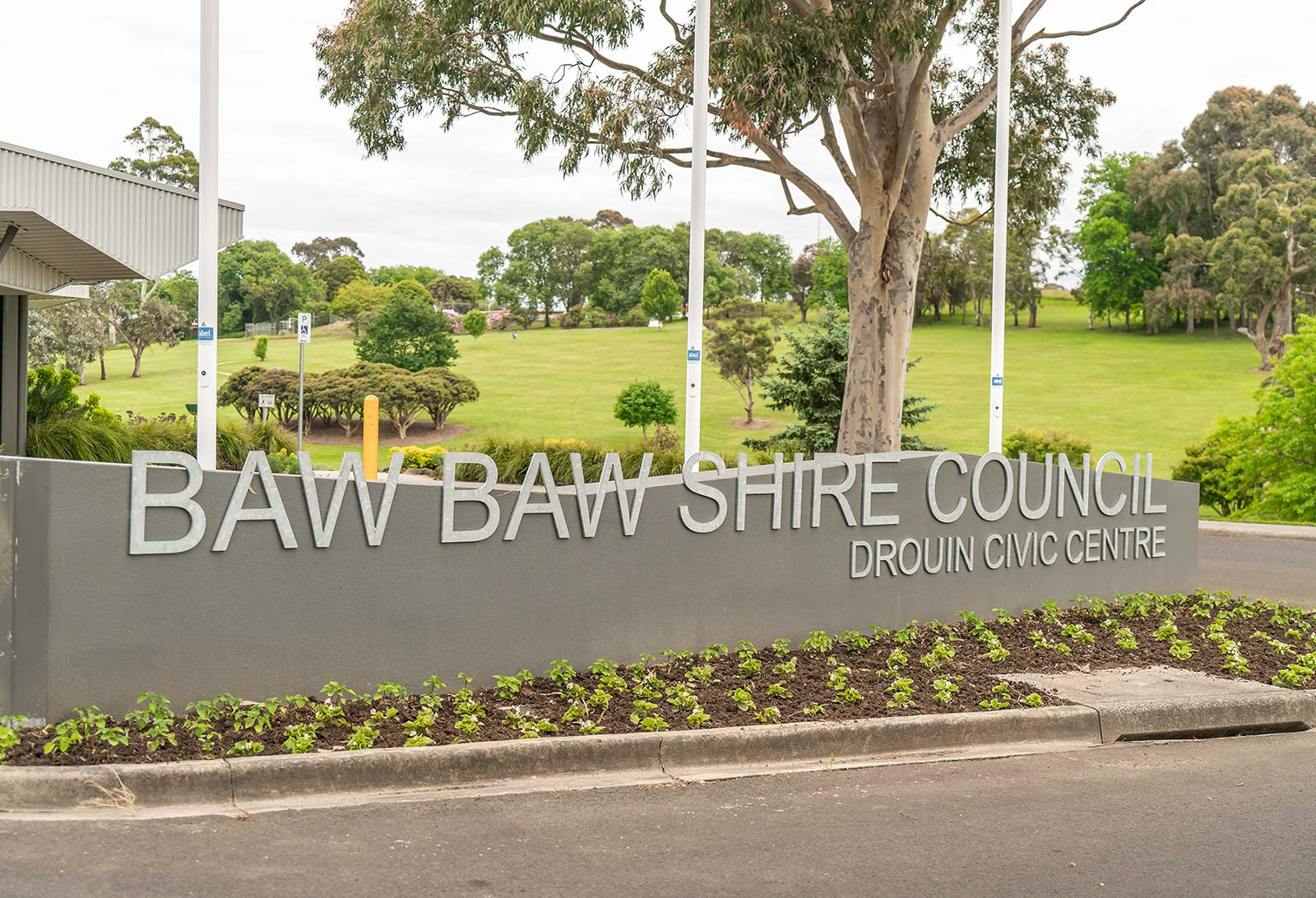 Image of outdoor sign with park and trees behind. Sign says Baw Baw Shire Council.