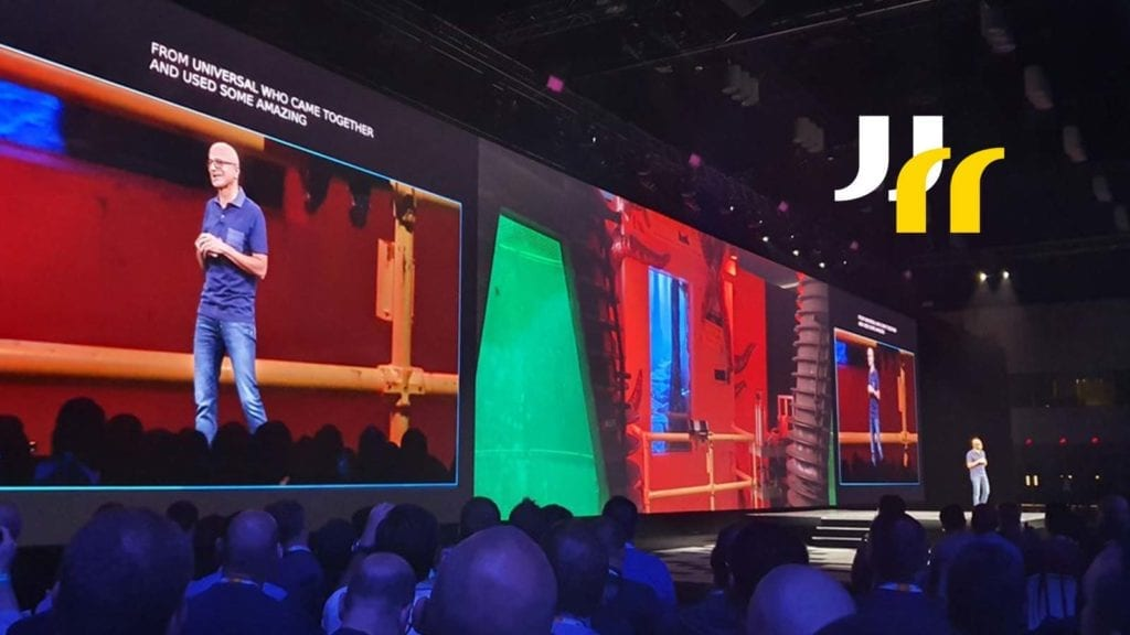 Image of man (Satya Nadella, Microsoft CEO) on large stage with huge screen behind with the man on stage on screen, taken at Microsoft Ignite 2019.