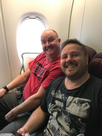 two men sitting in an airport, posing and smiling for the camera