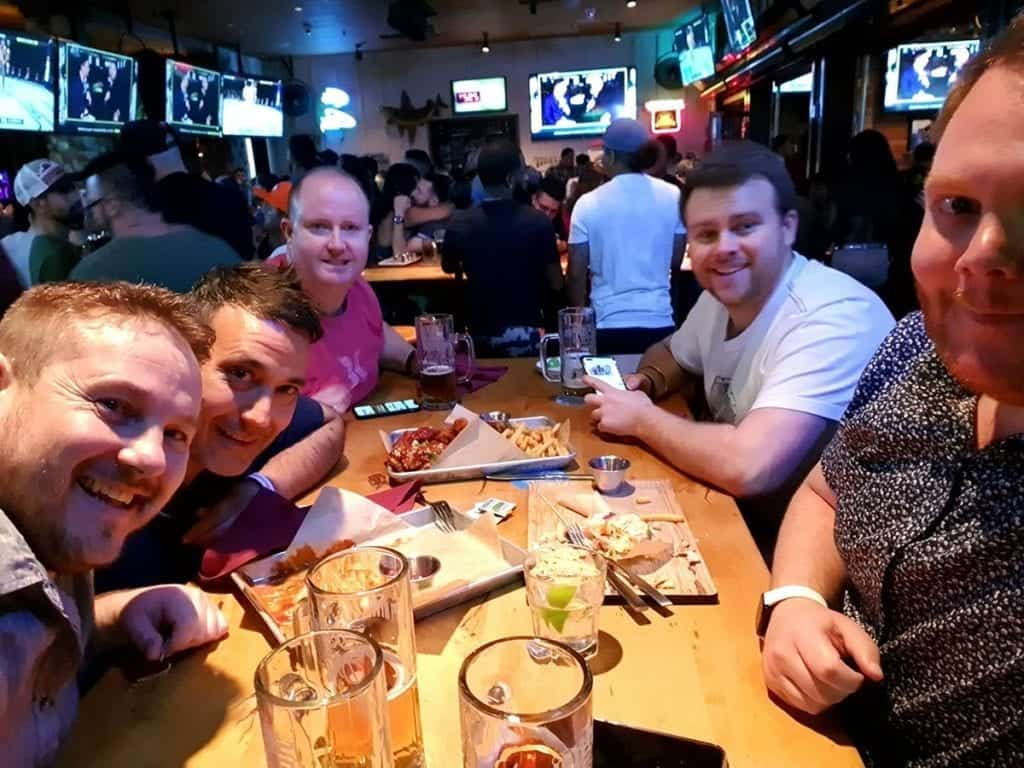 group of men around table in busy sports bar with many tv screens