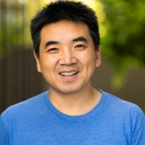 headshot of Zoom CEO Eric Yuan, smiling with a blue t-shirt