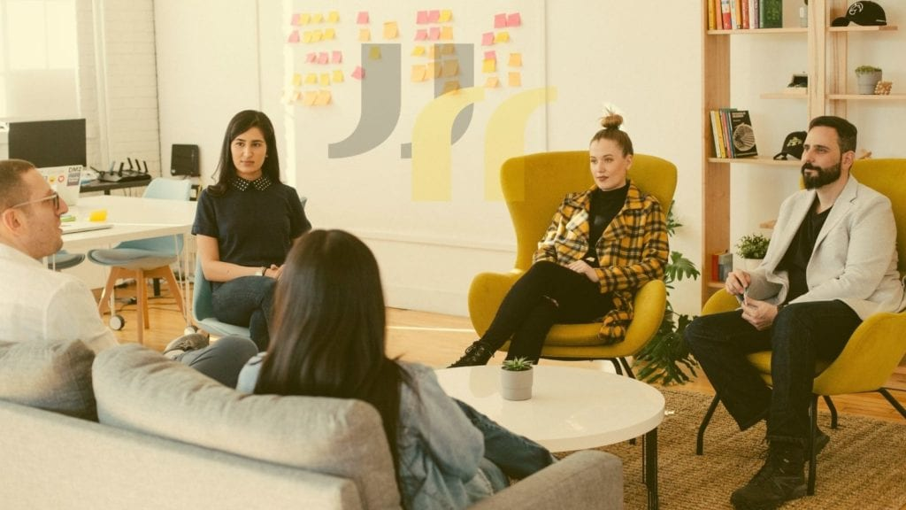 image of people meeting in a creative office, seated in a circle on comfortable chairs and couch